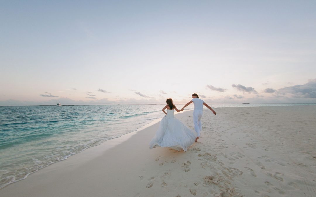 wedding on the beach, married couple running