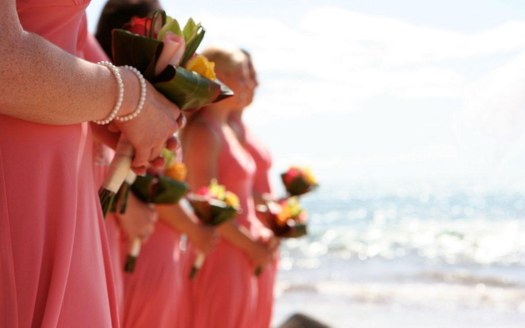 Women wearing pink bridesmaids beach dresses